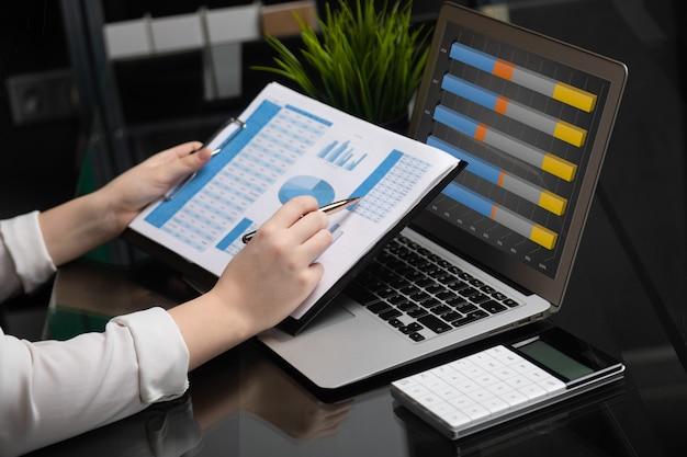 Бизнесмен, анализируя инвестиционные графики с ноутбуком. бухгалтерский учет