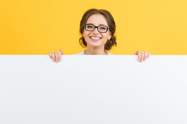 Портрет уверенно красивые счастливые улыбающиеся молодые бизнес-леди, показывая пустой рекламный щит на желтом фоне
