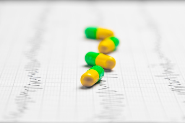 Разноцветные таблетки на листе экг