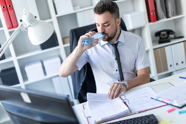 Мужчина сидит за столом в кабинете, работает с документами и пьет воду из бутылки.