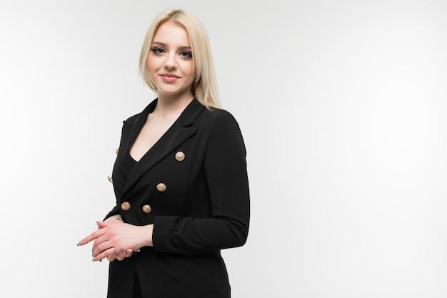 Очаровательная белокурая девушка в черном костюме на фоне
