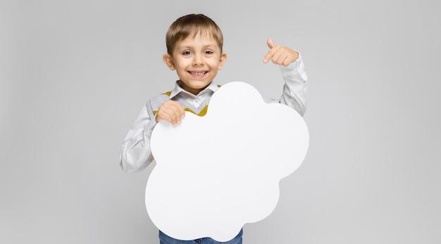 Стоит очаровательный мальчик в белой рубашке, майке в полоску и светлых джинсах. мальчик держит белый плакат в виде облака