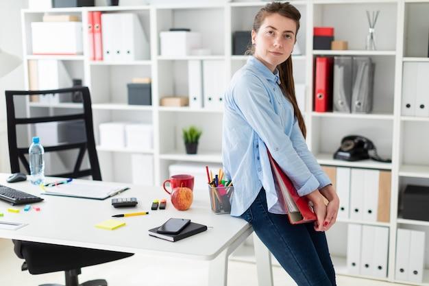 Молодая женщина в офисе стоит, опирается на стол и держит в руках красную папку с документами.