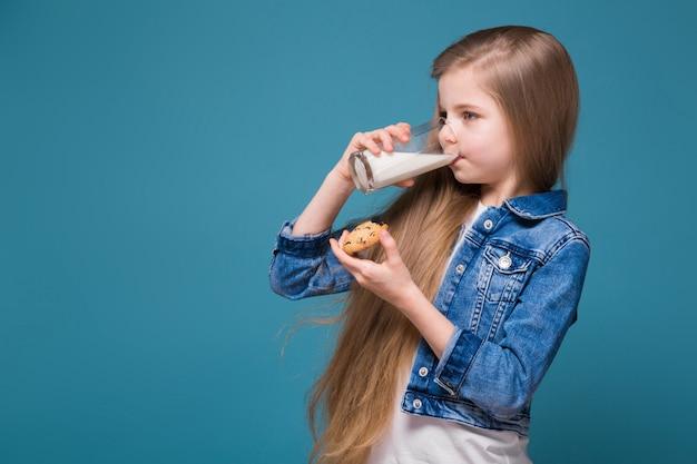 Маленькая милая девушка в джинсовой куртке с длинными каштановыми волосами держит тумблер