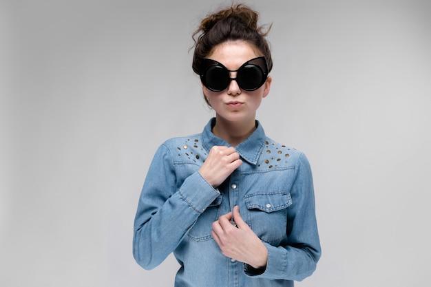 黒眼鏡の若いブルネットの女性。猫メガネ。髪はパンに集められます。女性はシャツを調整します。