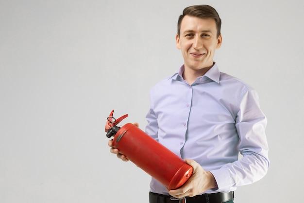若い男が彼の手で消火器を保持