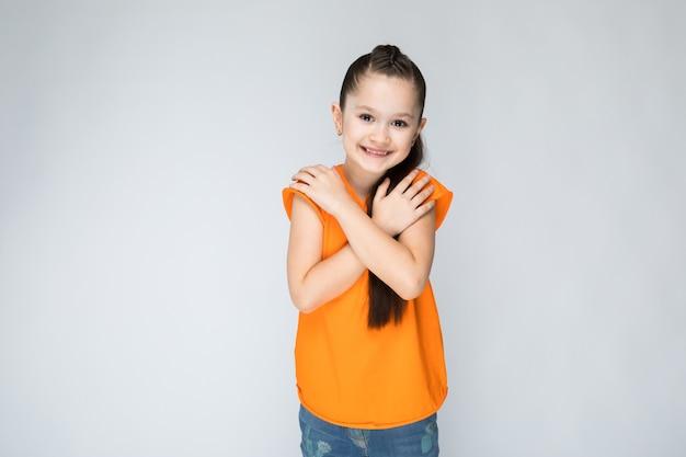 Девушка в оранжевой футболке и синих джинсах.