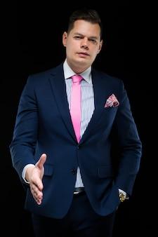 Портрет уверенно красивый бизнесмен, предлагая свою руку для рукопожатия на черном фоне