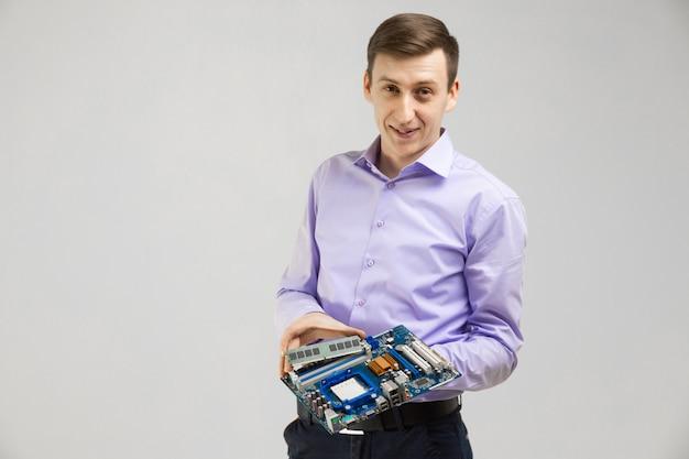 Молодой человек держит оперативную память и материнскую плату в руках, изолированных на светлом фоне