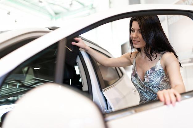 ディーラーのショールームで彼女の新しい車を見て美しいファッショナブルな黒髪