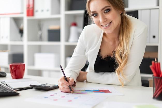 若い女性がオフィスのコンピューターデスクに座って、鉛筆を手に持って、チャートや図を操作します。