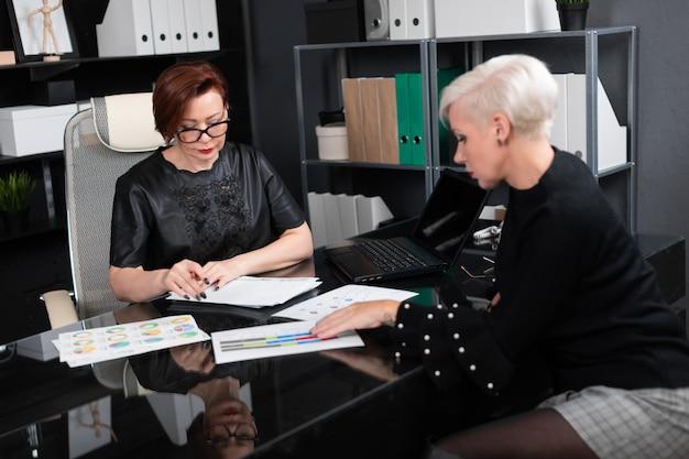 ビジネスの女性は、オフィスのデスクで図を議論します
