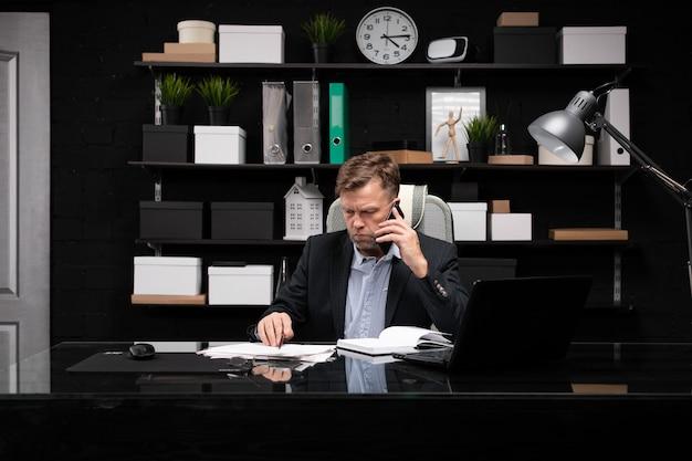 電話とドキュメントのコンピューターデスクで働くビジネス服の若い男