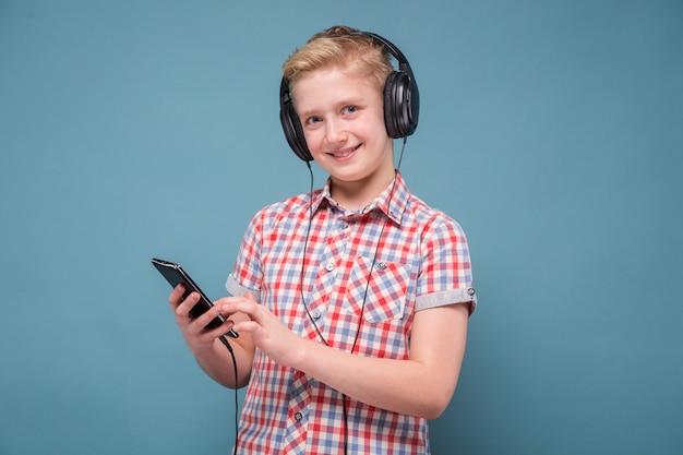 Студент с наушниками, глядя на дисплей мобильного телефона