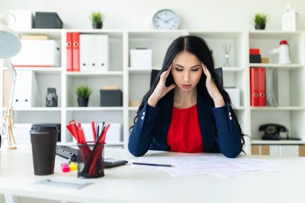 美しい若い女性がオフィスのテーブルに座って、頭の後ろで手をつないでいます。