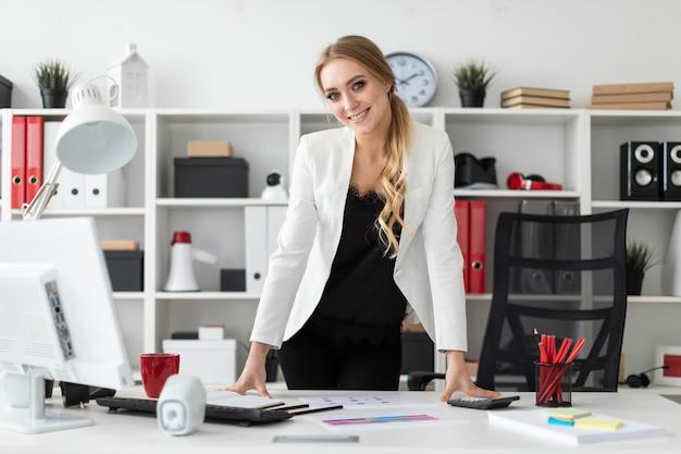 若い女性がコンピューター机の近くのオフィスに立っています。