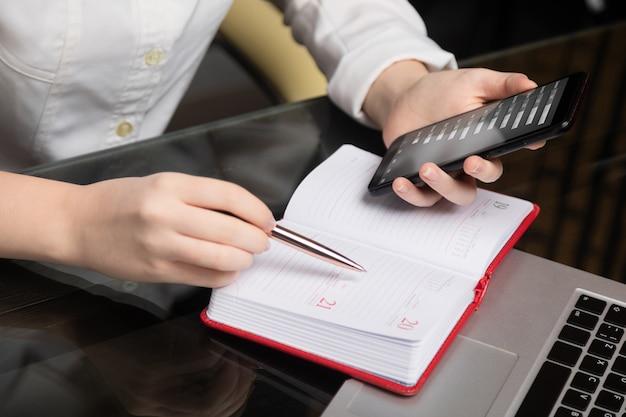 携帯電話を保持している若い実業家の手のクローズアップと日記にメモを作る