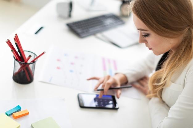 Молодая женщина сидит за компьютерным столом в офисе и рассчитывает на калькулятор на телефоне.