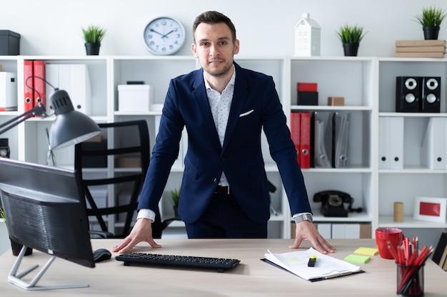 若い男がテーブルの近くのオフィスに立ち、手を彼に置きます。