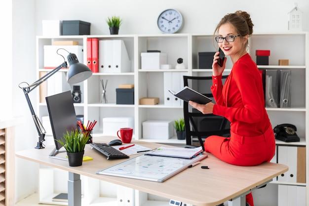 Молодая девушка села на стол в своем кабинете
