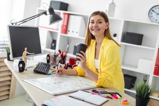Молодая девушка стоит возле стола и держит стакан кофе и маркер.