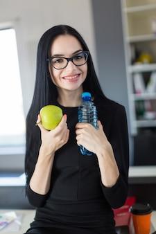 黒のドレスとメガネの美しい若い実業家は、オフィスのテーブルの上に座るし、青リンゴとボトルを保持