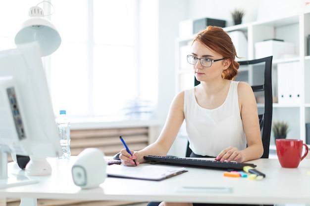Красивая маленькая девочка в офисе работая с ручкой, документами и компьютером.