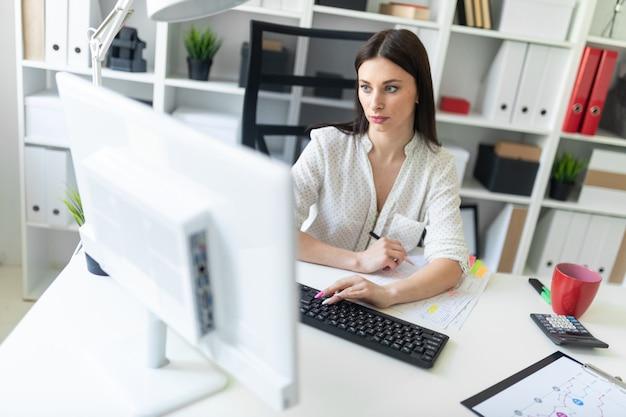Молодая девушка работает в офисе с документами и компьютером.