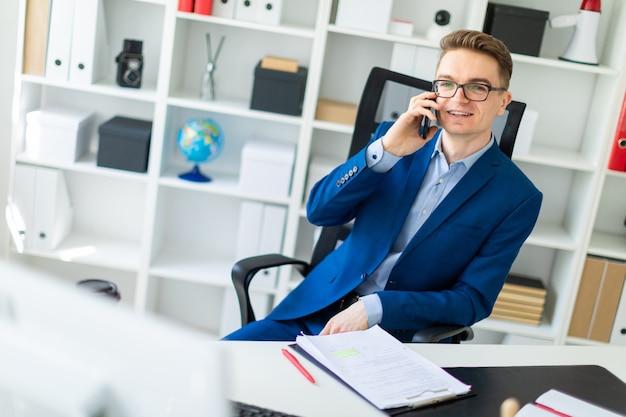 Молодой человек сидит за столом в кабинете и разговаривает по телефону.
