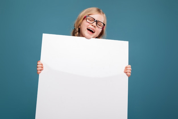ピンクのシャツ、黒いズボン、眼鏡のかわいい女の子は空のポスターを保持します