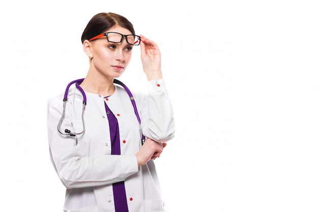 白い背景の上の上げられた眼鏡の若い美しい女性医師