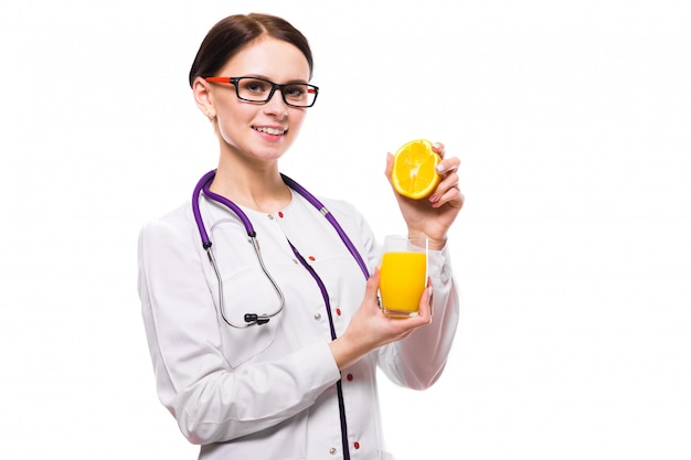 女性栄養士は、白い背景の上の彼女の手でセクションとフレッシュジュースのガラスでオレンジを保持します。