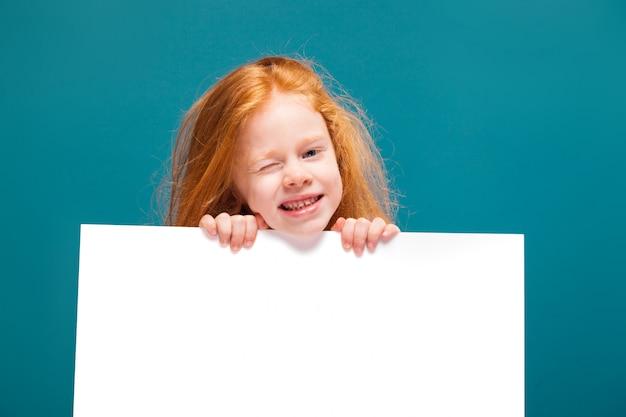 長い髪のティーシャツでかわいい美少女はきれいな紙を保持します。