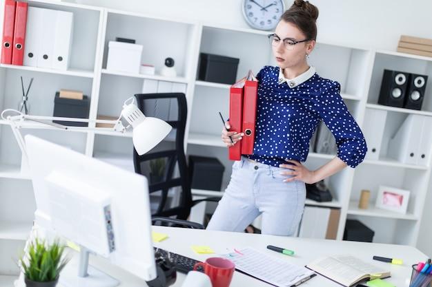 Молодая девушка в очках стоит в кабинете возле стола и держит папки с документами.