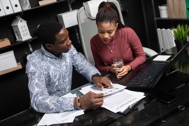 Двое молодых чернокожих обсуждают свои дела, используя диаграммы, сидящие за столом в офисе