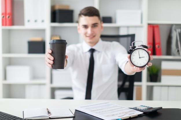 オフィスのテーブルに座って、コーヒーと目覚まし時計を保持している若い男。