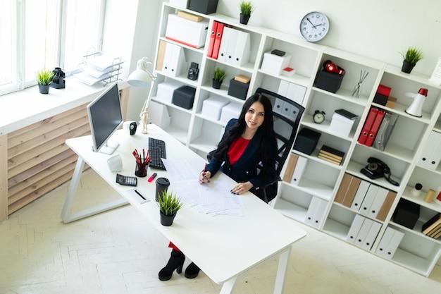 美しい少女は、テーブルのオフィスに座って、ドキュメントを塗りつぶします。