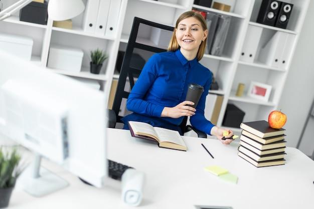 若い女の子がコンピューターの机に座って、コーヒーと黄色のマーカーが付いたグラスを手に持っています。