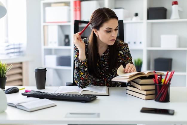 Молодая девушка сидит в офисе за компьютерным столом и работает с книгой.