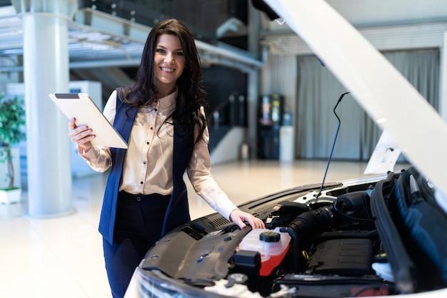 美しい販売マネージャーは、ディーラーセンターでタブレットの助けを借りて新しい車を検査します。