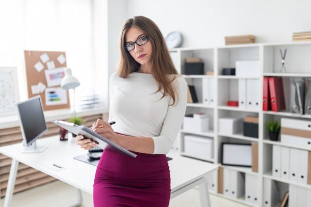 Молодая девушка стоит возле компьютерного стола и держит планшет с листами для записей.