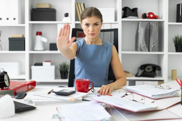 若い女の子がオフィスの机に座って、手のひらを前に伸ばします。