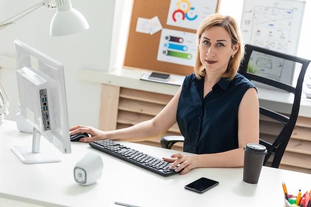 Молодая девушка работает за компьютером.