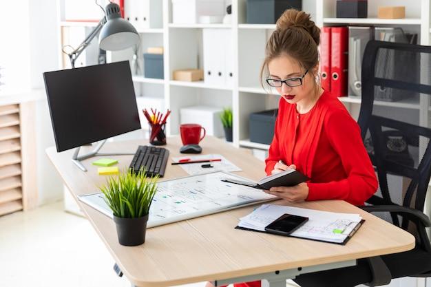 若い女の子がオフィスのテーブルに座り、マーカーを手に持ってメモ帳を操作します