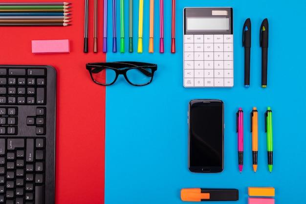 スマートフォン、電卓、ステッカー、ペンとビジネスデスクのフラットレイアウト構成