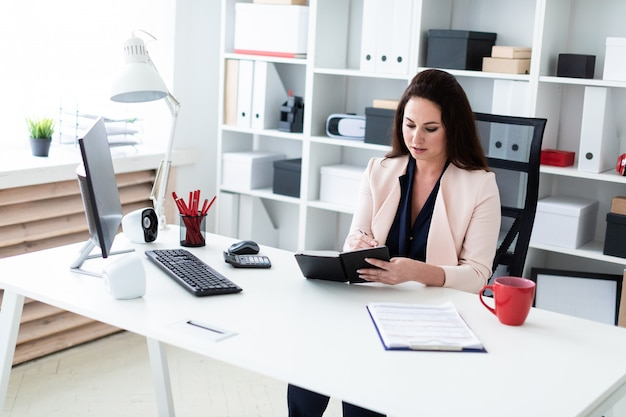 Молодая девушка сидит за компьютерным столом, держит ручку и работает с ноутбуком
