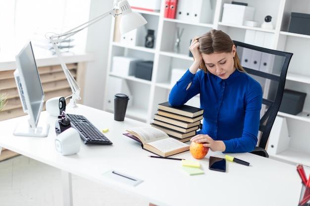 若い女の子がコンピューターの机に座って、頭に手をかざします。