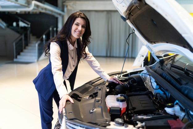 Красивая распродажа осматривает новую машину в автосалоне автосалона