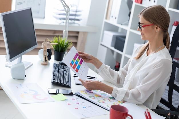 若い女の子がオフィスのテーブルに座って、チャート、図、ドキュメントを操作します。
