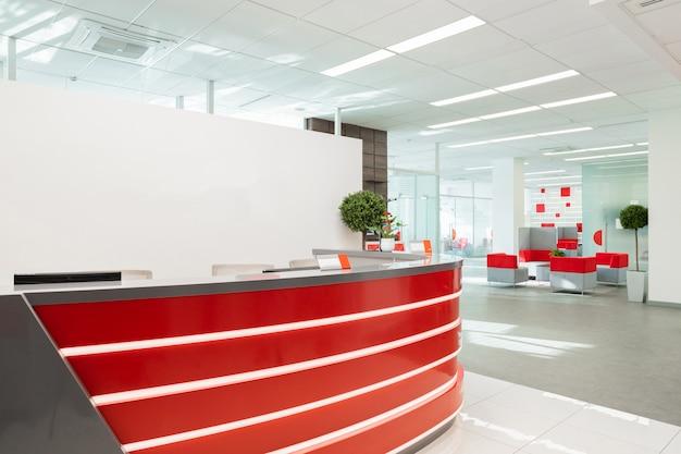 Приемная для посетителей современного офиса с красно-белым интерьером